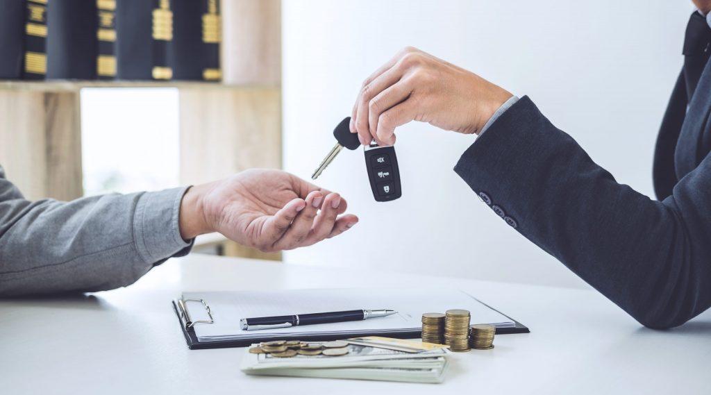 Mão passando uma chave de carro para outra mão